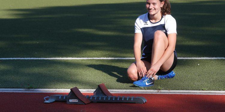 Das Bild zeigt die Athletin Amelie Dierke sitzend auf der Grünfläche neben einer Tartanlaufbahn.